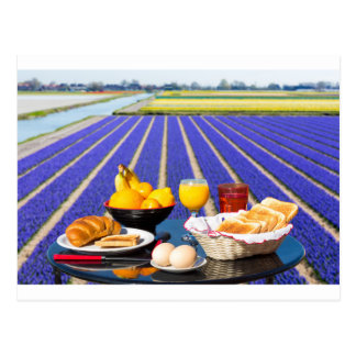 Table with food and drink near flowers field postcard