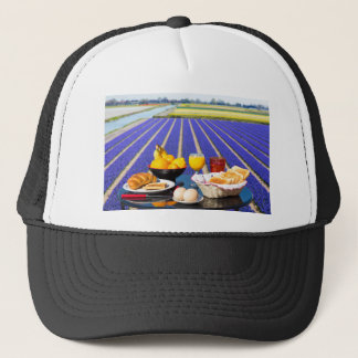 Table with food and drink near flowers field trucker hat