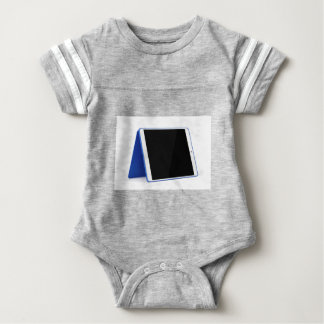 Tablet computer on white baby bodysuit