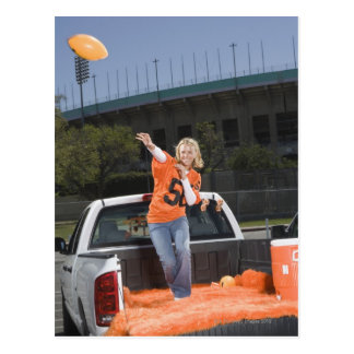Tailgating woman throwing football postcard