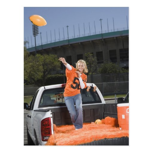 Tailgating woman throwing football post cards