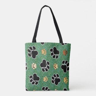 Tan and black paw print on green grass tote bag