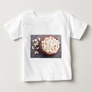 Tasty and healthy raw cashew nuts in a brown bowl baby T-Shirt