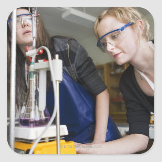 Teacher assisting student in laboratory square sticker