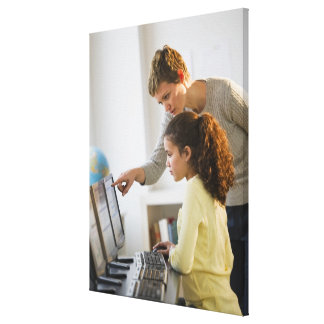 Teacher helping student in computer lab stretched canvas prints