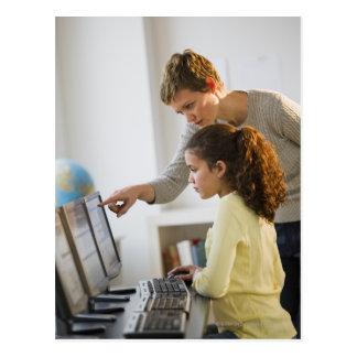 Teacher helping student in computer lab postcard