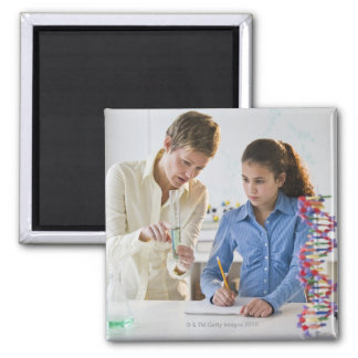 Teacher helping student in science lab square magnet