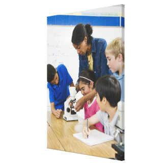 Teacher helping students use microscope in canvas print