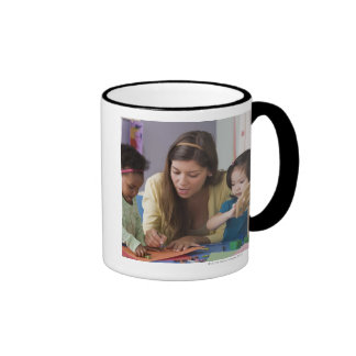 Teacher helping toddlers color at daycare mugs