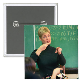 Teacher talking and pointing at front of 15 cm square badge