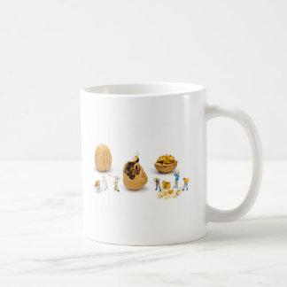 Team of miniature figurines transporting walnut coffee mug