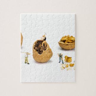 Team of miniature figurines transporting walnut jigsaw puzzle