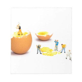 Team of miniature human figurines transporting egg notepad