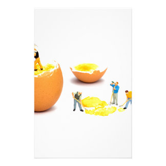 Team of miniature human figurines transporting egg stationery