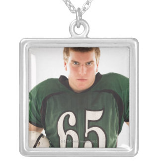 Teen football player holding helmet, portrait necklace