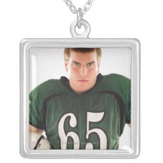 Teen football player holding helmet, portrait square pendant necklace