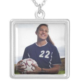 teen girl soccer player holding soccer ball necklace