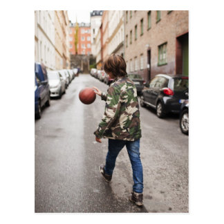 Teenage boy dribbling basketball postcard