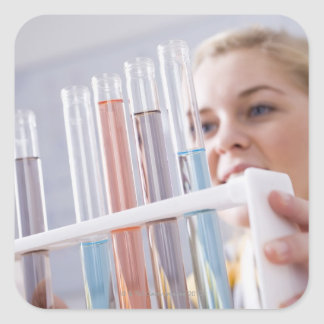 Teenage girl holding rack of test tubes square sticker