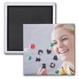Teenage girl looking at molecule model square magnet