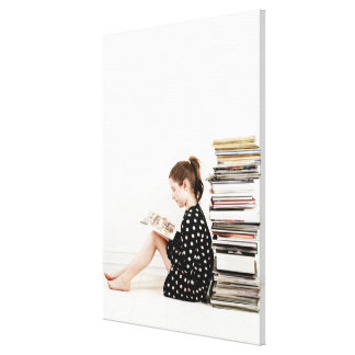 Teenage girl reading comic strip by pile of canvas prints