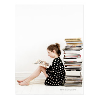 Teenage girl reading comic strip by pile of postcard