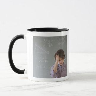 Teenaged boy in front of blackboard with math mug