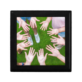 Ten arms of children in circle with palms of hands gift box