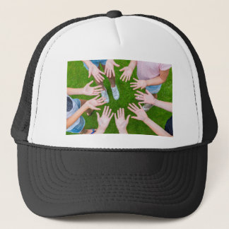 Ten arms of children in circle with palms of hands trucker hat