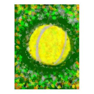 Tennis ball rests on the grass postcard