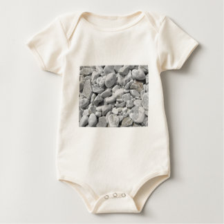 Texture of pebbles from a beach shore baby bodysuit