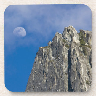 The moon rises and shines through the clouds drink coaster