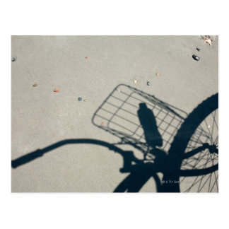 The shadow of a bicycle with a bottle of water postcard