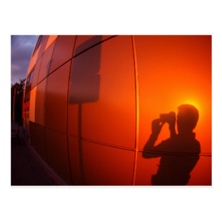 The shadow of a man on a red-orange wall, who phot postcard