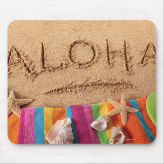 The word Aloha written on a sandy beach, with Mouse Pad