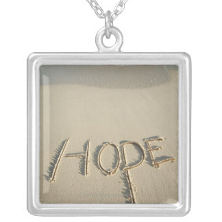 The word 'Hope' sand written on the beach with Silver Plated Necklace