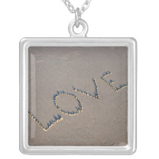 The word Love spelled out in the sand. Custom Jewelry