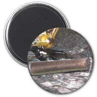 The yellow snowplow sits at rest in the wood 6 cm round magnet