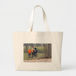 Three children on a cycle at the side of the road bags