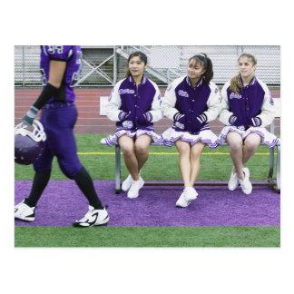 Three female cheerleaders (16-18) watching postcard