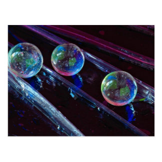 Three glass marbles rolling on smooth surface postcard