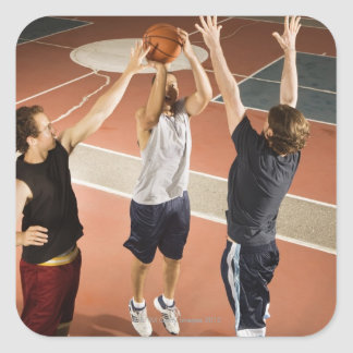 three men in athletic clothing playing stickers