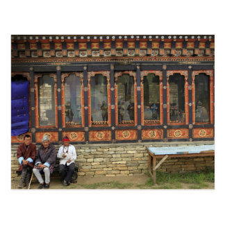 Three men sit on a bench at the Memorial Chorten Postcard