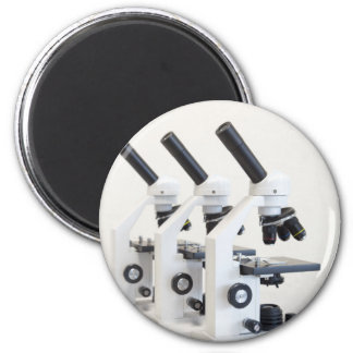 Three microscopes in a row isolated on background 6 cm round magnet