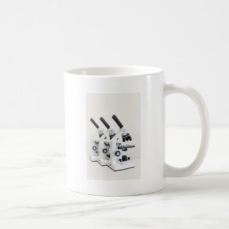 Three microscopes in a row isolated on background coffee mug