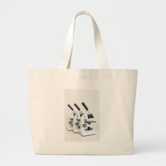 Three microscopes in a row isolated on background large tote bag