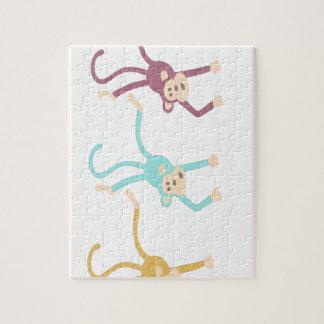 Three monkeys playing puzzles