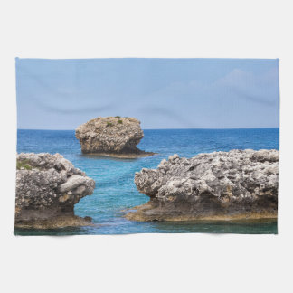 Three separate rocks offshore in sea tea towel