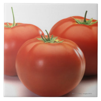 Three tomatoes on counter, close-up large square tile