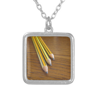Three used pencils on wooden table silver plated necklace